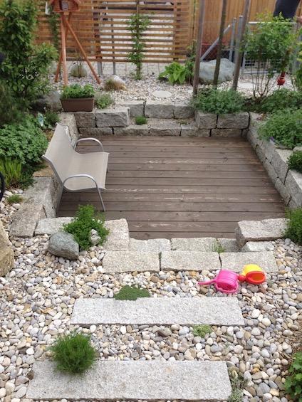 Die extrem kleine Gartenfläche wurde mit einem Holzdeck am Haus, einem kleinen versenkten Sitzplatz im hinteren Bereich sowie einer Bepflanzung mit Gehölzen und Stauden in Kiesbeeten sehr abwechslungsreich. (Poing bei München)