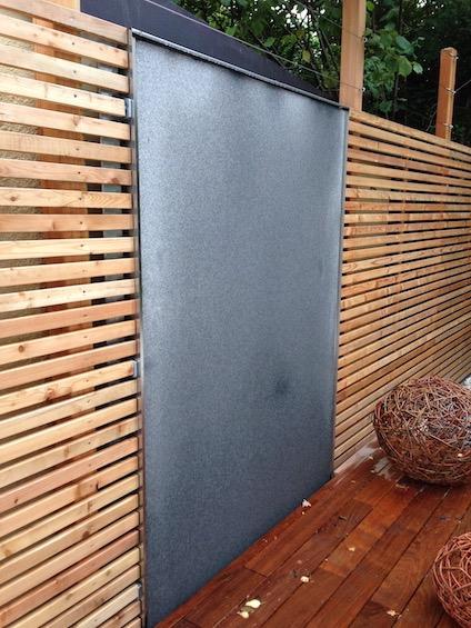 Wasserwand aus dunklem Granit, eingelassen in eine Wand aus Holz. (München - Solln)