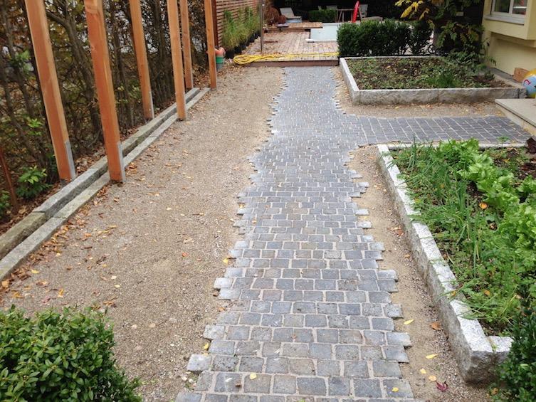 Weg aus dunklem Granit mit ausgefransten Rändern, wassergebundene Decke und mit Granit eingefasste Gemüsebeete 20cm erhöht. (München - Solln)