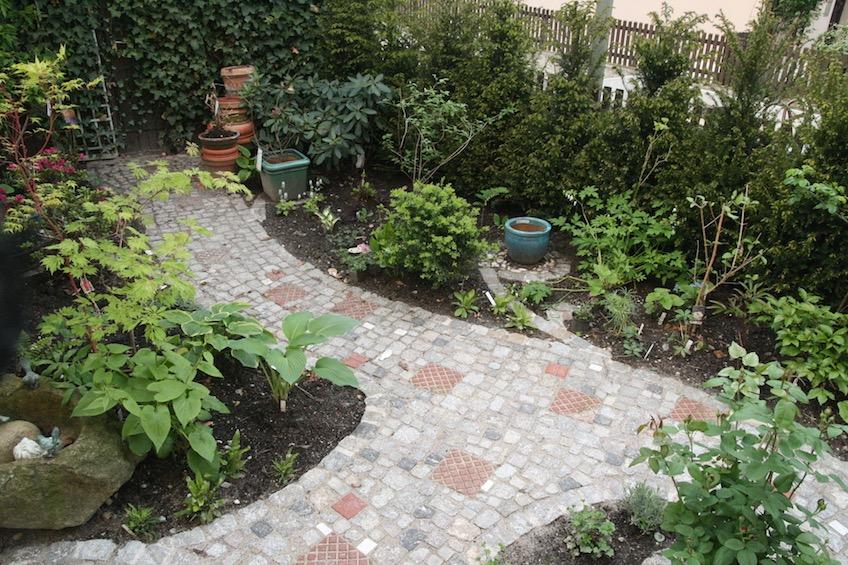 Weg aus buntem gemischten Pflaster. Gepflasterte Ranken aus Granit Kleinstein zum Stellen von Töpfen. Üppige Schattenbepflanzung. (Freising)