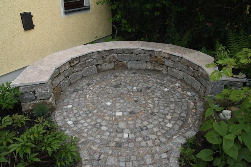 Sitzmauer aus Muschelkalk Mauersteinen, Belag mit eingepflasterter Schnecke aus Bummerln. (Freising)