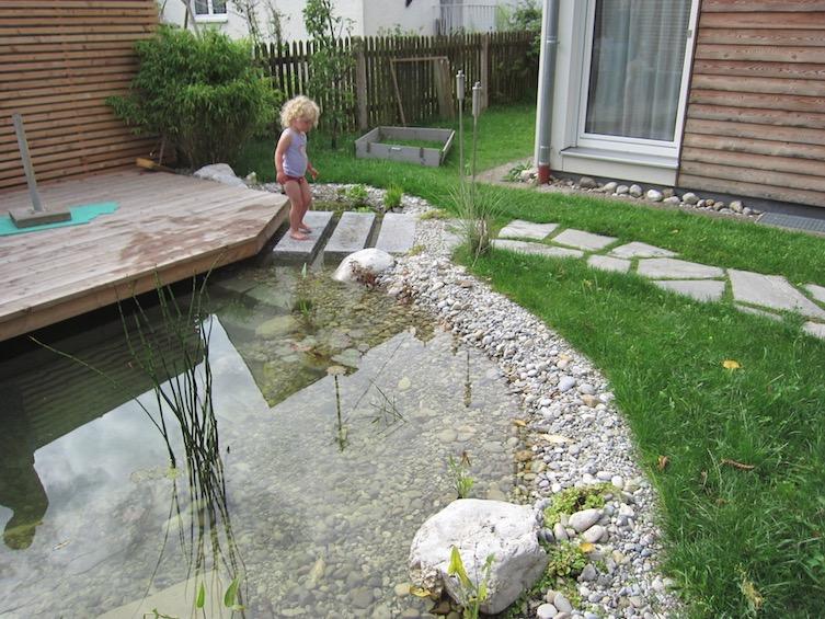 Teich mit über das Wasser ragendem Holzdeck aus Lärche. (München)