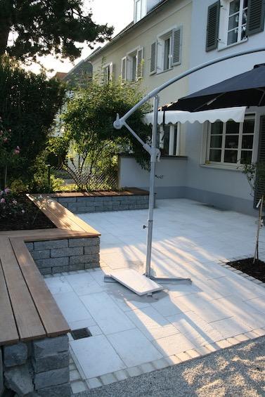 Lounge Terrasse mit Sitzmauer aus dunklem Granit, Holzauflage aus Bangkirai und Belag aus Rauriser Marmor. (München)