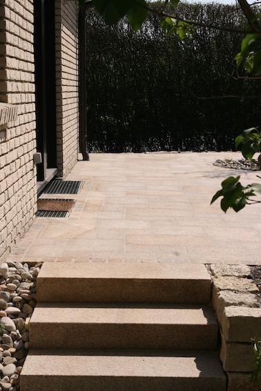 Terrassenbelag und Blockstufen aus gelbem Granit. Die Platten wurden im römischen Verband verlegt. (Pulling bei Freising)