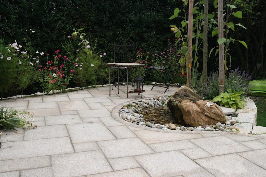 Terrasse mit organischen Schwüngen und Quellstein mit sichtbarer Wasserfläche. (Pulling bei Freising)