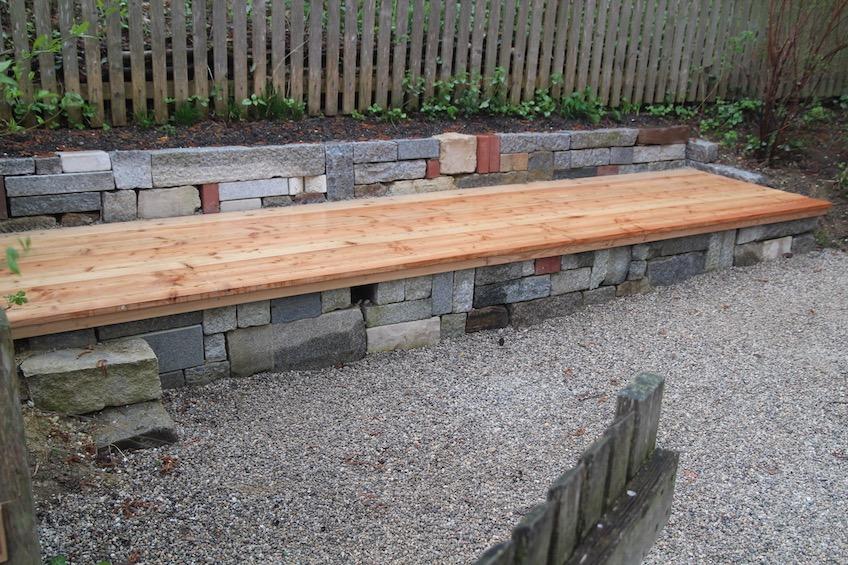 Mauer aus gemischten Steinen mit Holzauflage aus Lärche. (Freising)