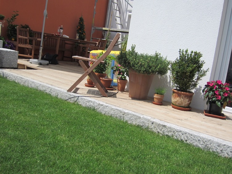 Eine Stufe von der Terrasse auf den Rasen kann optisch sehr reizvoll wirken. (Poing bei München)